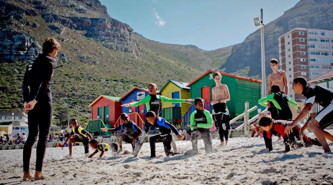Children learn to stand on their surfboards through volunteer surf coaching in South Africa